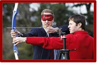 Prince William blindfolded and learning to aim an arrow using a camera tripod equipped with a tactile sighting device.