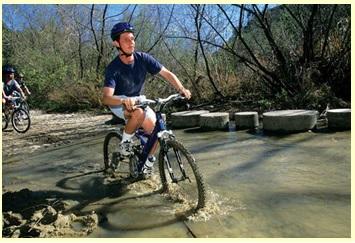 Daniel Kish mountain bikes through a stream.